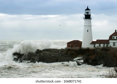 Sun breaks through the storm clouds as huge waves crash by Portland Head lighthouse in Maine during high tide.