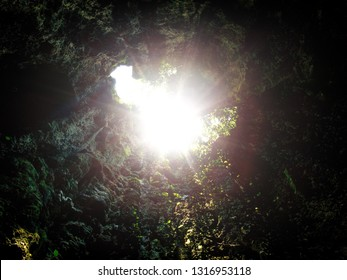Sun burst or sun flare coming from top of underground cave opening. Concept of success, hope in the darkness and light at the end of tunnel
