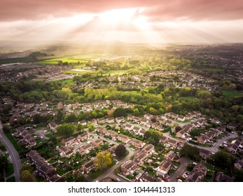 Sun bursting through clouds over traditional British houses with countryside in the background. Dramatic lighting and warm colours to give a homely effect.
