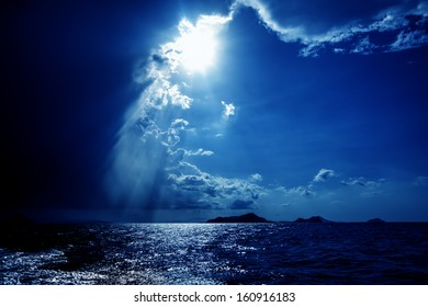 Sun bursting through dramatic skies over the ocean
