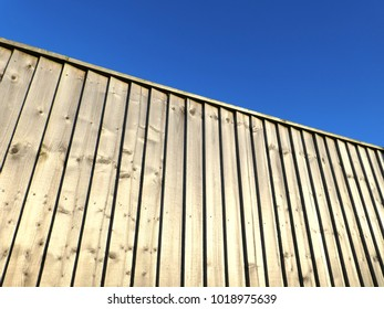 The sun casts shadows on wooded fencing panels against blue sky