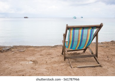 Sun chair on the beach facing the sea. View from the back.