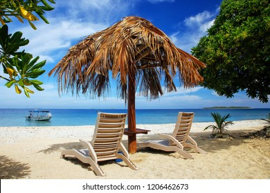 Sun chairs with thatched umbrella on a white sandy beach, South Sea Island, Mamanuca group, Fiji.