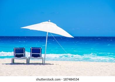 Sun chairs and umbrella on a tropical beach
