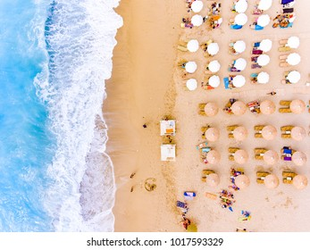 Sun chairs and umbrellas bird's eye view on sand beach in Greece