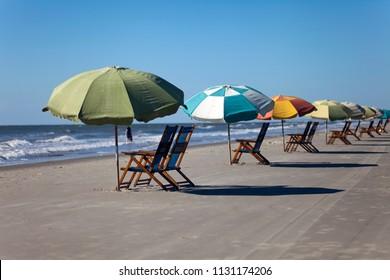 Sun chairs and sun umbrellas on a sandy beach against a clear blue sky in Galveston, Texas