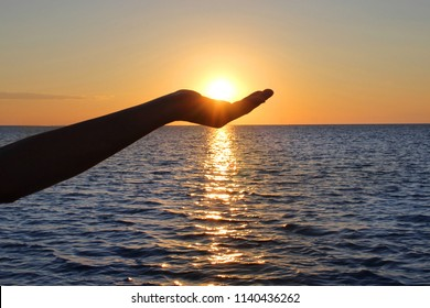The sun in a child's hand. Silhouette of hand holding sun