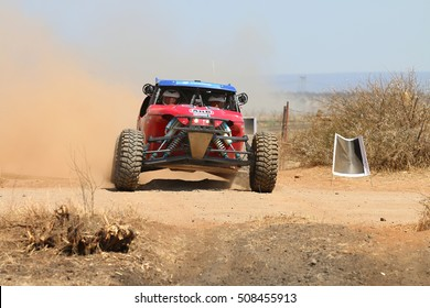 Sun City, South Africa - OCTOBER 1, 2016: Front view close-up of red Porter rally car pull away at road crossing in race at Sun City 450 Rally Racing event, Sun City, South Africa