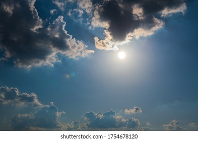 Sun and clouds in the dark blue sky (backlight)