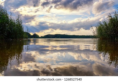 Sun and clouds in the dramatic sky are reflected in the lake. Natural background with clouds and water.