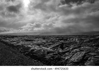 Sun, clouds and rain on lava plains at Kalapana, Volcanoes National Park, Big island, Hawaii in black and white
