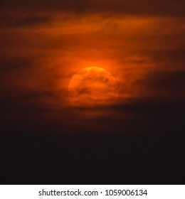 The Sun in cloudy sky at nightfall time in the summer season