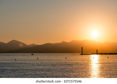 sun coming down and boat returning in a port, mountains silhouettes background, sunset landscape, Cannes, french riviera.