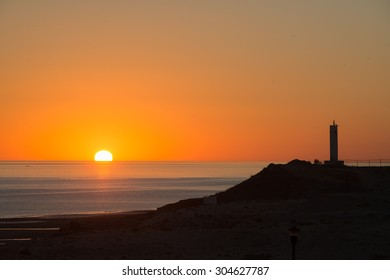Sun coming out behind the lighthouse