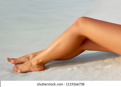 Sun Cream Concept. Closeup Of Beautiful Sexy Long Woman's Legs on the Beach. Perfect Hairless Smooth Soft and Silky Skin. Beauty Body Care Concept