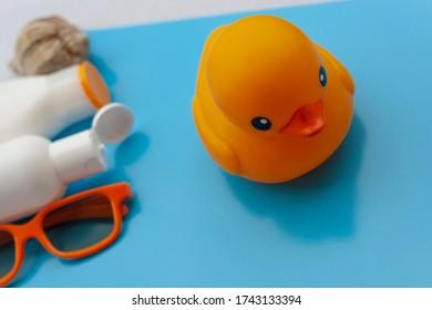 Sun cream, orange sunglasses, shells, toy orange plastic duck on a light blue background. Concept of summer, vacations, rest, sea.