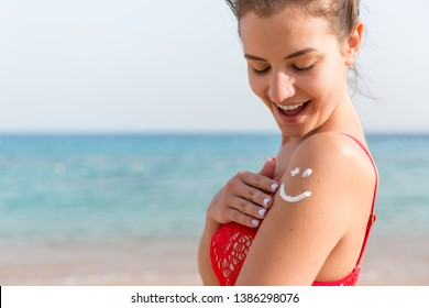 Sun cream over tanned woman's shoulder in the shape of smiling face.