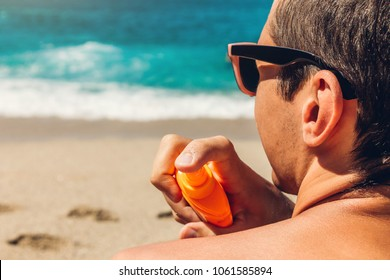 Sun cream protection. Man sprays sun cream on his shoulder. Skin care concept. Healthy skin on vacation.