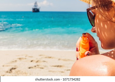 Sun cream protection. Woman sprays sun cream on shoulder. Skin care concept. Healthy skin on vacation.