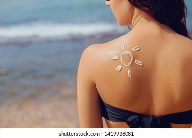 Sun cream. Suntan lotion beautiful woman applying on tanned shoulder in form of the sun. Sunscreen solar cream. Skin care. Sun protection.The Girl uses moisturizer sunblock