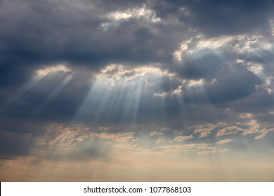 Sun crepuscular rays bursting through the clouds.