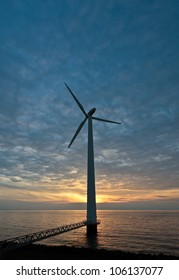 The sun disappears just behind a wind turbine along the seashore at sunset