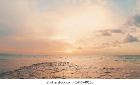Sun down sea shore background. Indian ocean beach seascape fond. Blue sky and yellow clouds over sea. Idyllic sun down on the beach. Destination sea shore sun down. Natural ocean beach landscape.