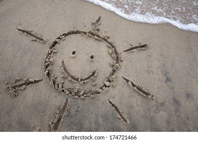 Sun drawing in the sand as waves approach, for a beach or summer vacation concept.