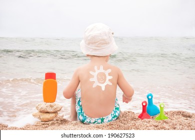 The sun drawing sunscreen (suntan lotion) on baby (boy)  back. Caucasian child is sitting with plastic container of sunscreen and toys on beach. Close up, outdoor, copyspace (Sharm El Sheikh, Egypt).