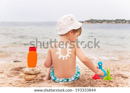 The sun drawing sunscreen (suntan lotion) on baby (boy)  back. Caucasian child is sitting with plastic container of sunscreen and toys on sunny beach. Close up, outdoor (Sharm El Sheikh, Egypt).