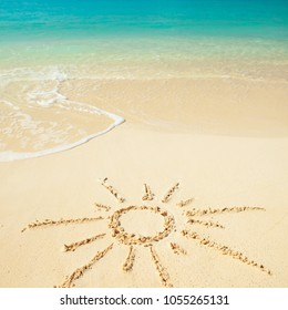 Sun drawn on sand of Tropical beach. Ocean beach background. White sand and crystal-blue sea. Ocean water nature, beach relax. Summer sea vacation. Sun protection concept