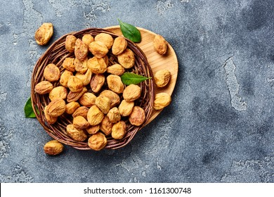 Sun dried apricots on gray concrete background. Top view of dried fruits with copy space.