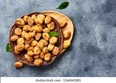 Sun dried apricots on gray concrete background. Top view.