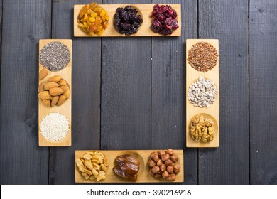 sun dried berry fruits, nuts and seeds on bamboo serving trays, frame composition, black wood table background