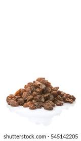 Sun dried dark raisins over white background