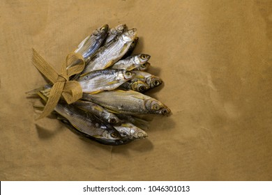 Sun dried fish. Fish on the brown craft paper. Bleak.