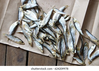 Sun dried fish on the brown paper. Soft focus.