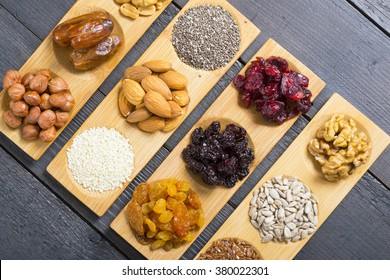 sun dried organic fruits, nuts and oil seeds on bamboo serving tray, black wooden table background