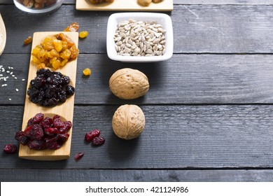 sun dried super foods, nuts and cereals on black wood table background