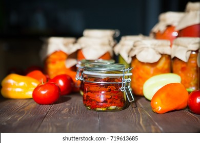 Sun dried tomatoes with olive oil in a jar. Preserved and fresh vegetables on home table. Various homemade conserves in glass jars