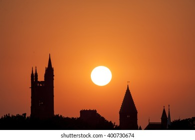 Sun drops behind silhouetted buildings of town center in Fairhaven, Massachusetts