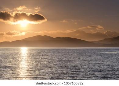 The sun drops below a cloud along Loch Fyne in Argyll Scotland one November afternoon