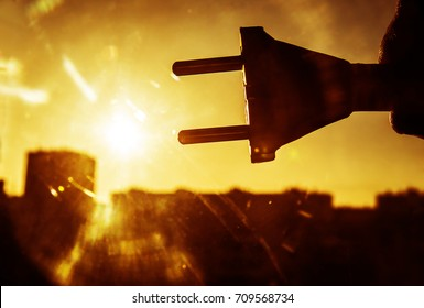 sun energy with plug connection ready to get power. silhouette of power socket against sun rays and sunny sky with houses. Urban backdrop. alternative Solar energy sign, symbol, idea and concept.