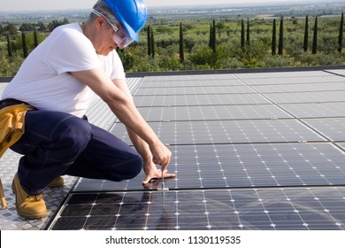 sun energy worker fitting photovoltaic panels
