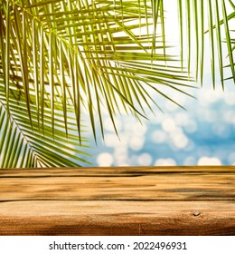 The sun, exotic palm trees and a wooden table on a beautiful hot summer day