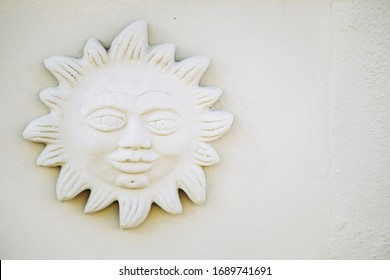 Sun and face sculpture on the facade of a house