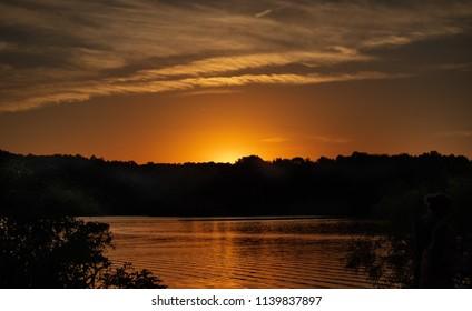 Sun Falling behind the Trees at Lake Logan, Ohio by Hocking Hills