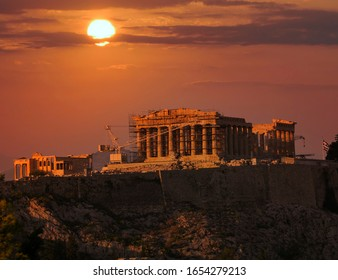 sun and fiery sky over Parthenon temple on Acropolis of Athens, Greece