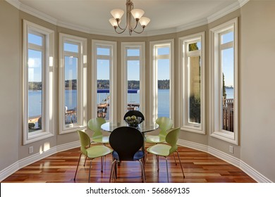 Sun filled breakfast nook features glass top table with black and green chairs atop glossy hardwood floor. Window wall presents picturesque view of Lake Washington. Northwest, USA