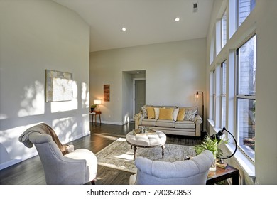 Sun filled family room in soft beige tones. The room is furnished with a lovely sofa topped with yellow pillows, two grey tufted armchairs and a round tufted ottoman atop a rug.
